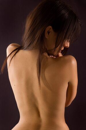 Naked torso of womans back body on dark backgrounds