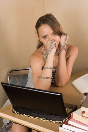 Young business woman at office with laptop linked with chain photo