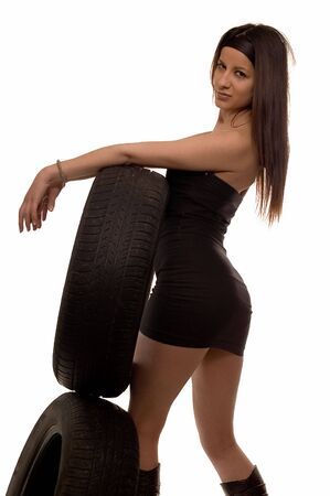 Young sexy girl holding a car wheel