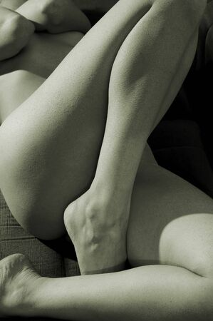 Naked girl with legs on first plane at monochrome photo