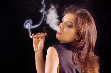 Young beautiful woman blowing smoke rings from cigar Stock Photo - 2489540
