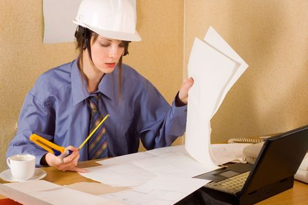 Woman architect with helmet on head and arch project at table Stock Photo - 2511252