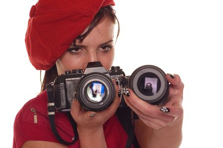 Young female photograpger holding photo camera and lenses for its