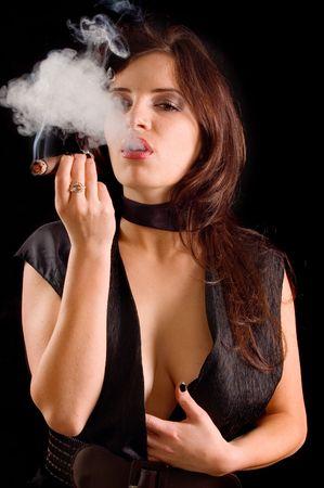 Beautiful woman smoking a cigar and blowing smoke  Stock Photo