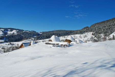 Winter rural scene on mountais with wooden house and haystack photo