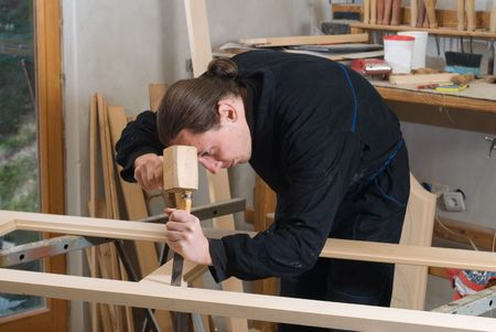Young carpenter working in his workshop on carpenters bench