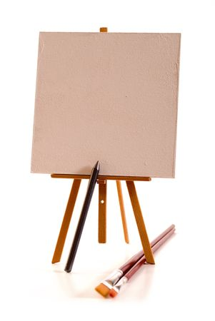 The easel  with blank canvas and huge pencil and brushes, focus on top of pencil