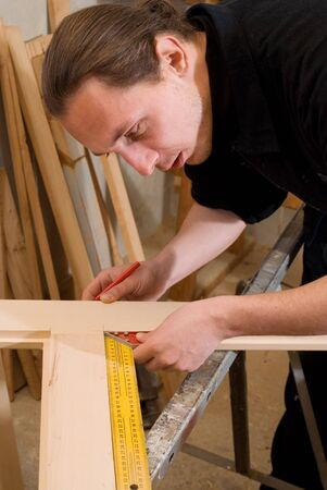 Carpenter doing measure with protracor on door  Stock Photo