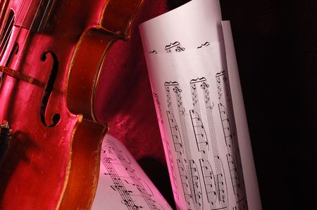 transcribe: Composition of music notes written on paper with fragment of old red violin Stock Photo