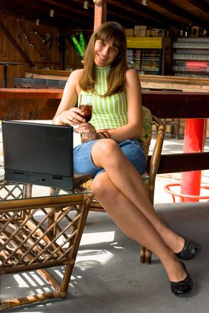 Young woman in restaurant with laptop and glass of juice photo