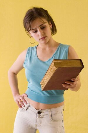 yelow: Young student girl holding her books on yelow backgrounds