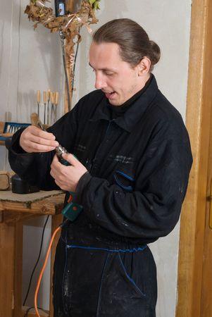 borer: Young carpenter change borer in his workshop  Stock Photo