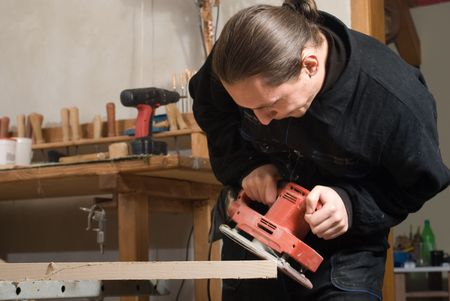 Young carpenter working in his workshop with polishing mashnie Stock Photo