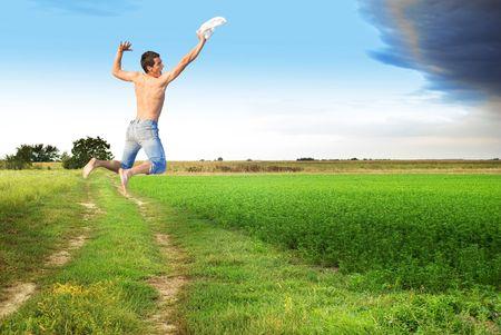 clody: Young man jumping to meet clody skies through flat ground