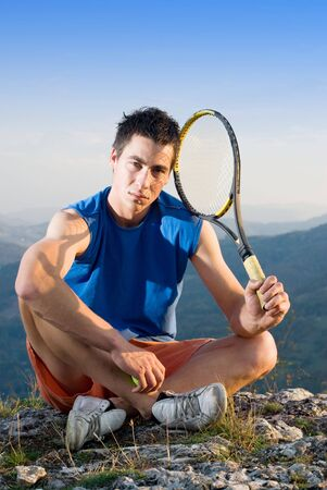 Young man take a break during training tennis on top of the rock