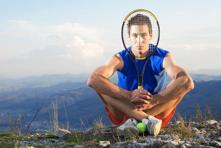 Young man holding racket tennis in front of his face, sitting on rock