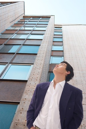 Tall building against blue sky and business man photo