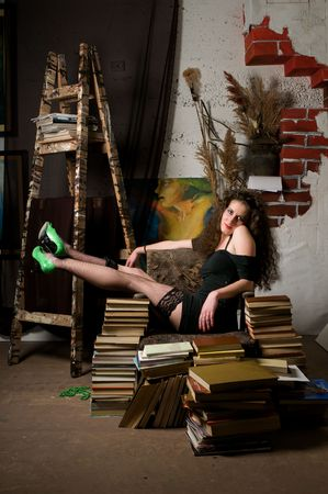 atelier: Woman sitting on armchair of books at fine arts atelier