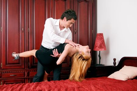 Young lovely embrace couple dancing at bedroom photo