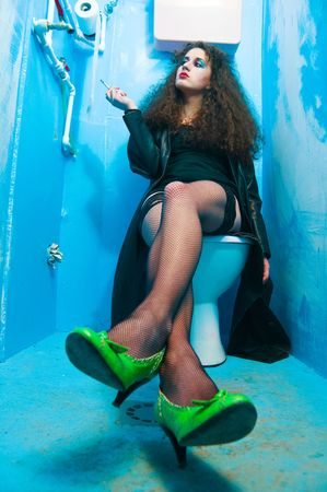 Woman sitting on toilet bowl at neglected and dirty public blue wc Stock Photo - 6710533