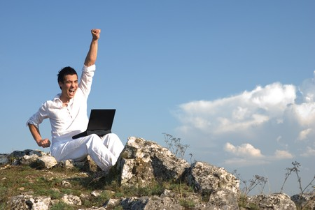 Young man using his laptop, sitting on the  rocky     photo