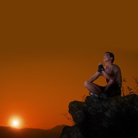 Man practicing yoga exercises on top of the mountain photo