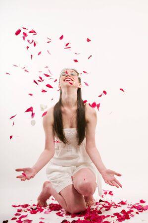 Caucasian woman throw petals of red roses