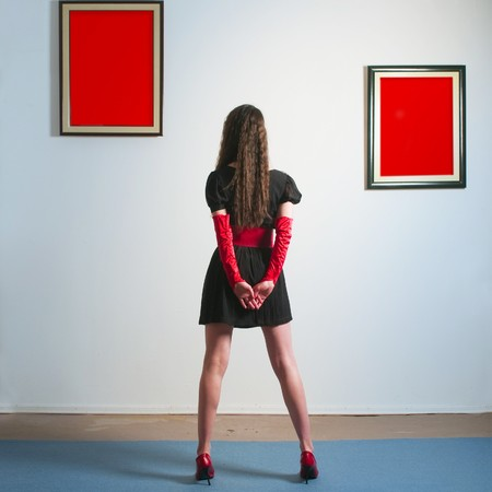 Woman inside a gallery infront of two red picture and looking at them