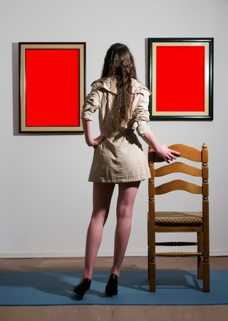 Woman standing inside a gallery infront of two picture frames and looking at them. photo