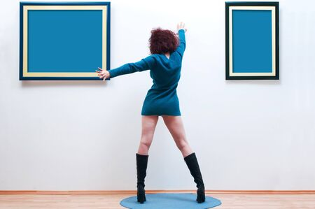 Woman posing inside a gallery infront of two blue picture frames, rear view photo