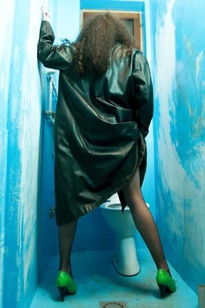 dirty girl: Donna dal cappotto di pelle wearning indietro nel wc blu pubblico trascurate e sporco