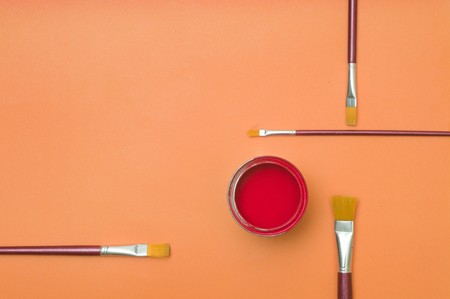 Red colors paint in tin with paint brushes on orange backgrounds photo