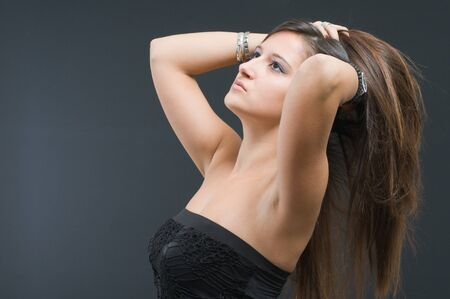 Attractive woman with long brown hair on black Stock Photo - 8048387