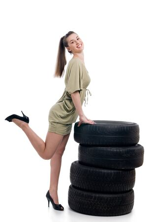 Young sexy woman like vulcaniser with a automobile tire photo