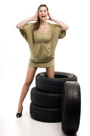 Young sexy woman with automobile tire and screaming photo