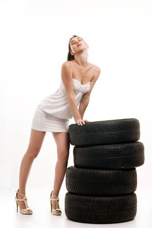 Young sexy woman like vulcaniser with a automobile tire Stock Photo - 8048539