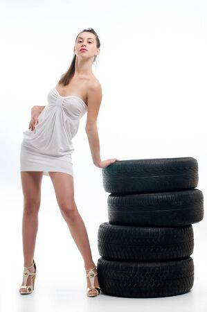 Young sexy woman like vulcaniser with a automobile tire Stock Photo