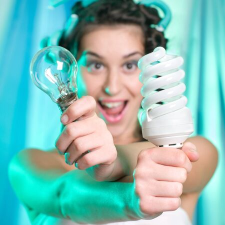 Woman holding and looking at energy saving compact fluorescent lightbulb and classical bulb photo