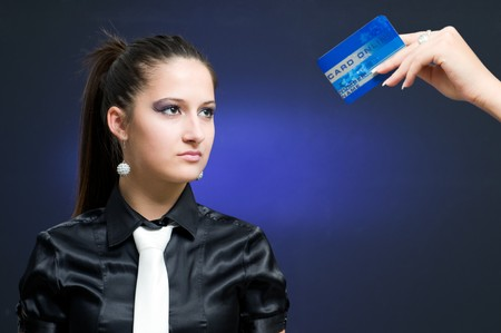 Young businesswoman looking at online credit card, focus on woman photo