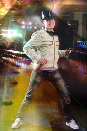 Disc jockey dancing with microphone and headphones  at night club photo