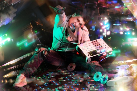 Disc jockey sitting on CDs with electronic mixer and microphone at night club