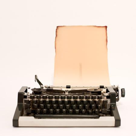 typewriter: Vieja m�quina de escribir con papel quemado en ella