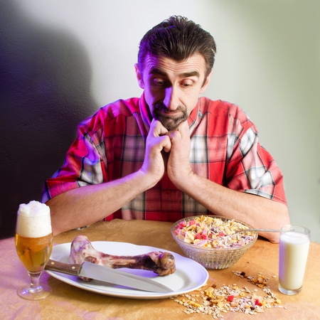 Scene with health, vegetarian food, smoked meat, glass of milk and beer. A man have a dilemma what take to eating photo