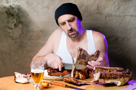 Man cutting with knife smoked ribs of pork and drinking beer photo