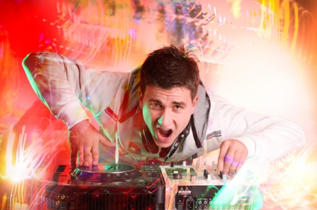 Disc jockey spinning and mixing records at night club photo