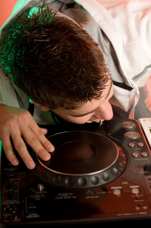 Disc jockey work with electronic mixer and mixing records at night club photo
