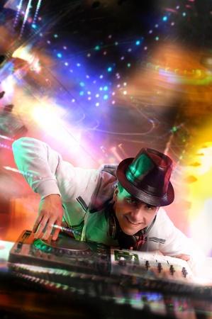 auriculares dj: Trabajo de Disc jockey con mezclador electr�nico y registros de mezclas en club nocturno Foto de archivo