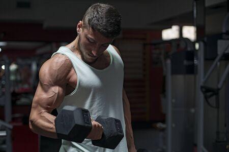 Uomo muscolare costruttore di formazione il suo corpo con manubri
