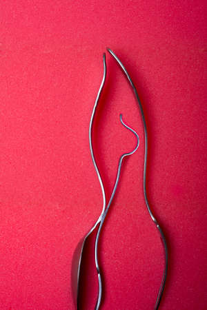 spongy: Male and female human figure from bent fork and spoon on red spongy background Stock Photo