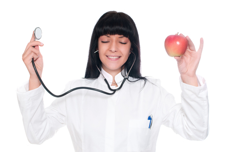eye service: A doctor holding apples and stethoscope with eyes closed, Stock Photo
